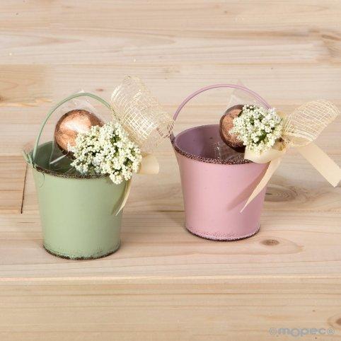 Grüner und lila Metalleimer mit Blume und Bonbon